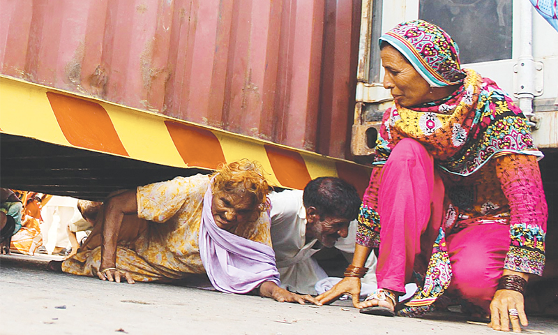 LAHORE: People crawl under a container to cross a bridge on Saturday. The administration placed containers on the Ravi bridge to stop PAT supporters from going to their leader's Model Town residence.—Online