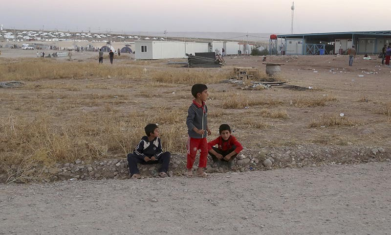 Displaced Iraqi boys from the Yazidi community wait at the entrance of the camp of Bajid Kandala  as they look for their family members who they became separated from during their escape, at Feeshkhabour town near the Syria-Iraq border, in Iraq Saturday, Aug. 9, 2014. — Photo by AP