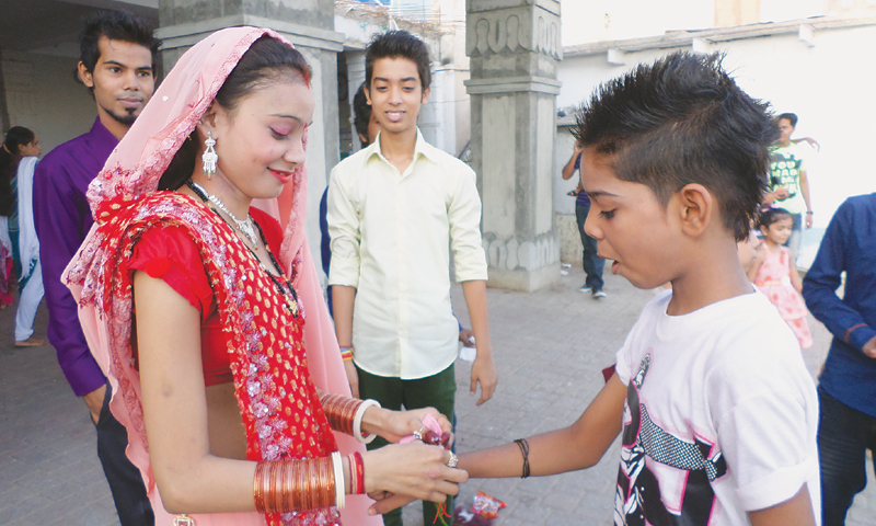 A newly-wed woman ties a ceremonial thread to the wrist of a boy, the younger brother of her husband, to mark the Raksha Bandhan ceremony at the Shree Lakshmi Narayan Mandir on Sunday. — Photo by writer