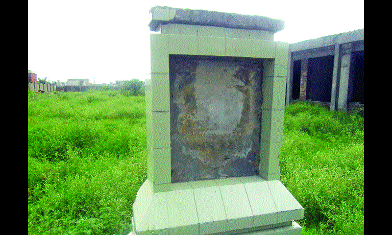 The two incomplete government colleges in Dhoke Syedan. The other picture is of the damaged plaque, which once announced the establishment of the institutions in the locality. — Dawn