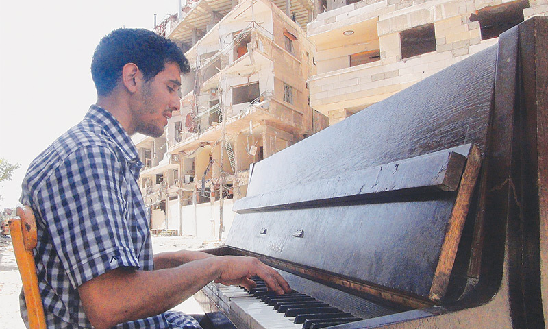 AYHAM al-Ahmed, a resident of Damascus Yarmuk Palestinian refugee camp, plays the piano in the middle of the street near destroyed buildings.—AFP