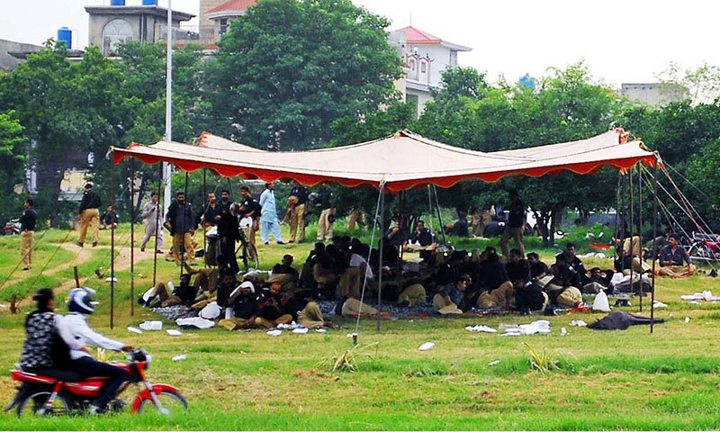 Police personnel sit on the grass near Faizabad to avert any untoward incident. -Online photo