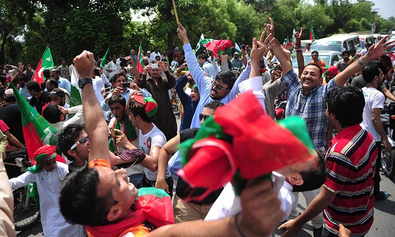 PTI supporters cheer as they gather outside the residence of Imran at the start of their protest march against government in Lahore on August 14, 2014. — Photo by AFP