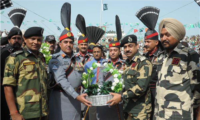 Pakistan Rangers exchanging sweets with Indian Border Security Forces. — Photo by AFP