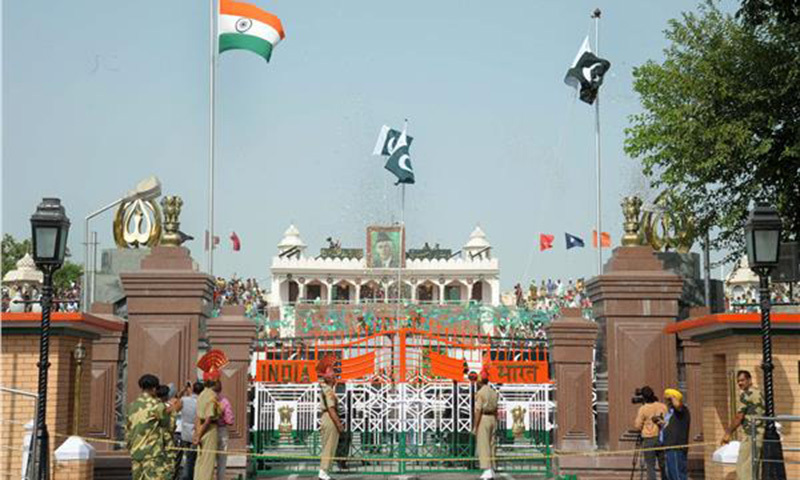 A Pakistani Ranger (top) unfurls the Pakistani national flag as Indian Border Security Force (BSF) personnel (bottom) watch during a ceremony to celebrate Pakistan's Independence Day at the India Pakistan Wagah border post on August 14, 2014. — AFP