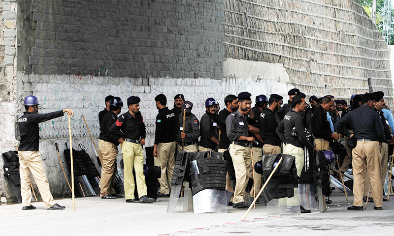 Policemen stand guard on a major highway in Rawalpindi August 14, 2014. - Reuters