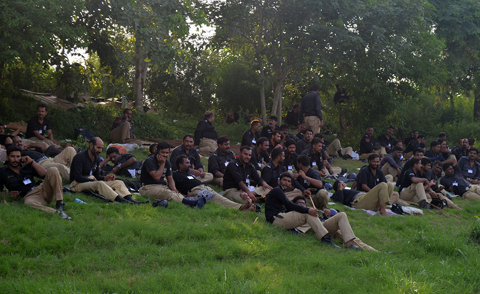 Police personnel on security duty take a rest on the grass near Faizabad Interchange as they wait for the 'Azadi' march to reach Islamabad.—Photo by Irfan Haider