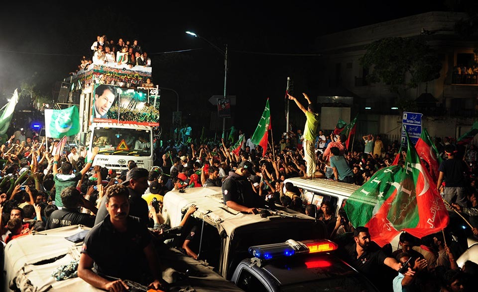 A truck (L) Pakistan Tehreek-i-Insaf chief Imran Khan as he heads a protest march from Lahore to Islamabad against the government, in Lahore on August 14, 2014. — Photo by AFP