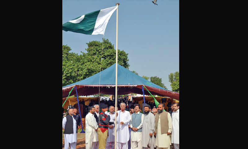 Chief Minister Pervez Khattak hoists national flag at the police lines in Peshawar on Thursday. — Dawn
