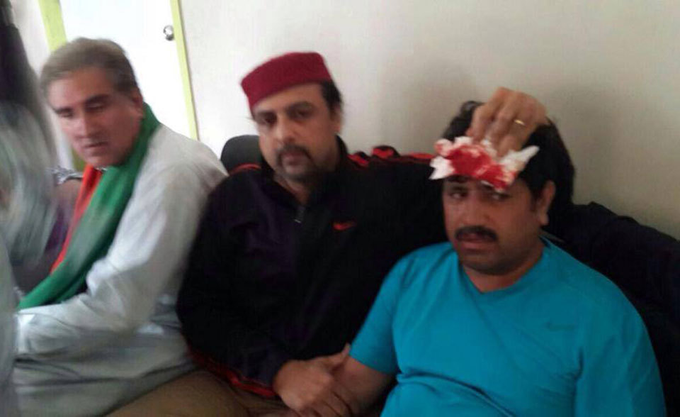 Shah Mehmood Qureshi and Salman Ahmed with an injured PTI worker. — PTI's official page