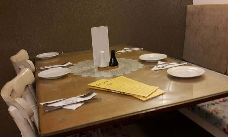 Table in the corner with the bright yellow menu – Photo by author