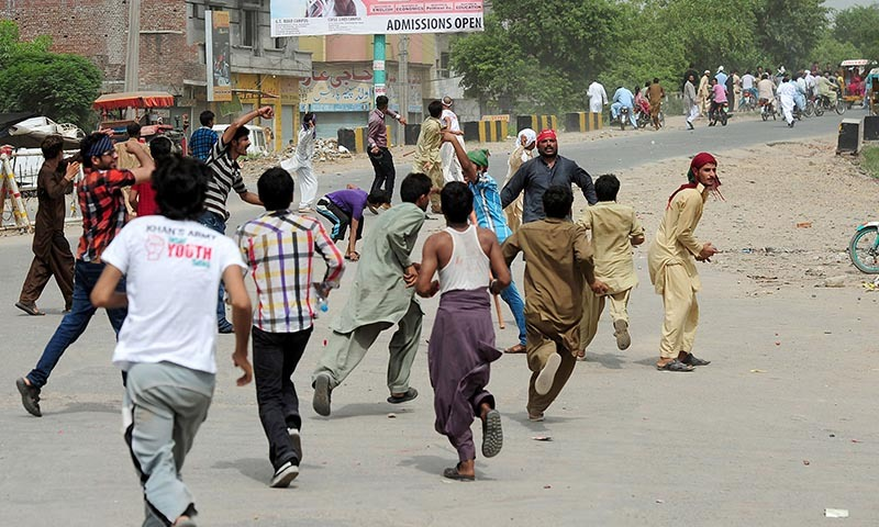 Pakistan Tehreek-i-Insaf (PTI) supporters throw stones toward the supporters of ruling Pakistani Muslim League- Nawaz (PML-N) during protest march to Islamabad, in eastern city of Gujranwala in Punjab province on August 15, 2014.— Photo by AFP