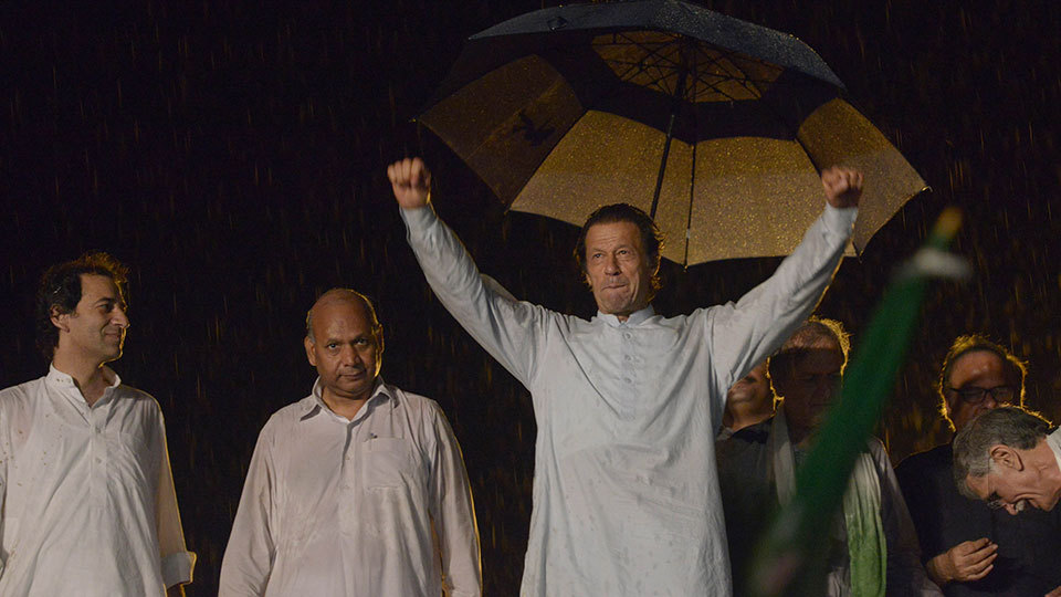 PTI chief Imran Khan (R) gestures upon his arrival at a rally in Islamabad on August 15, 2014. — Photo by AFP