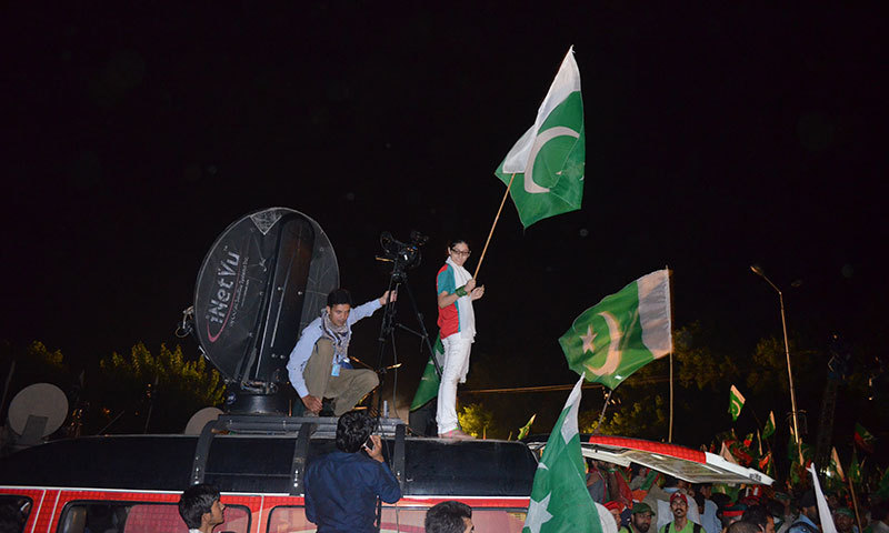 The image shows a PTI supporter standing on the roof of a vehicle in Islamabad. — Photo by Irfan Haider
