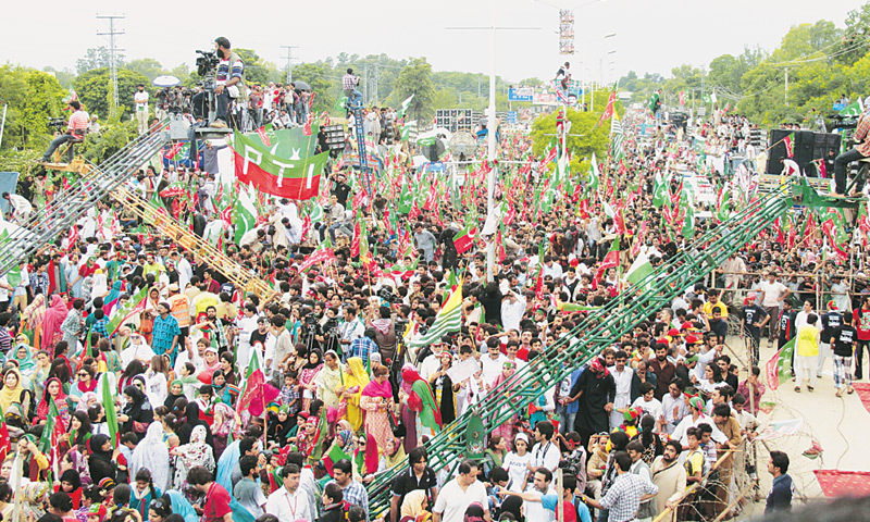 PTI supporters wave flags at the party's sit-in.—Tanveer Shahzad / White Star