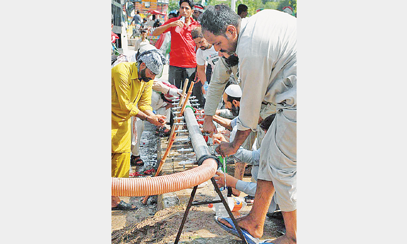 PAT workers wash themselves at a temporary water supply system set up at the sit-in site in Islamabad. — Online