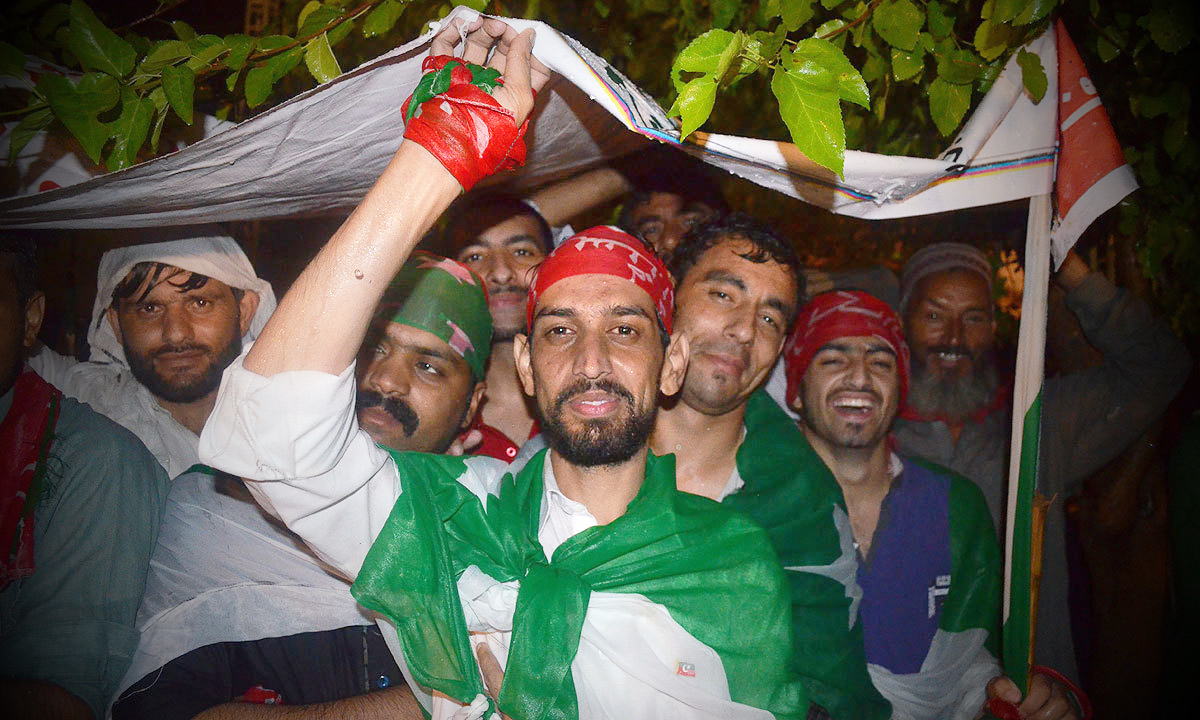 PTI supporters from Peshawar protect themselves from the rain - Photo by Irfan Haider