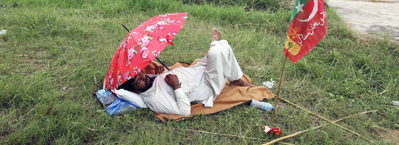 A PTI supporter sleeps under an umbrella - Reuters