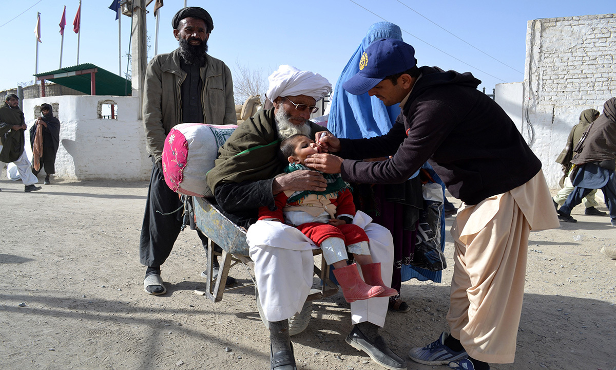 An anti-polio medic vaccinates a child of an Afghan family at  Chaman border linking it with Afghanistan. The cases of polio victims have risen in the region recently and the vaccination drives still continue.