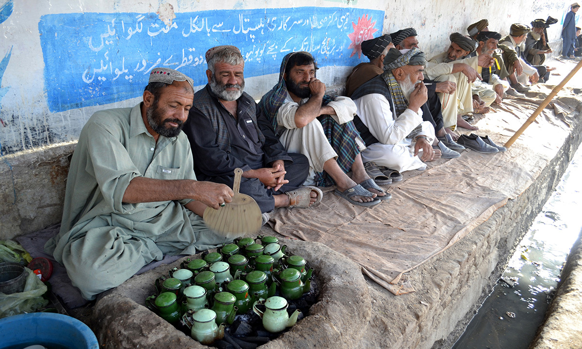 Residents sit around a tea stall in a bazaar.