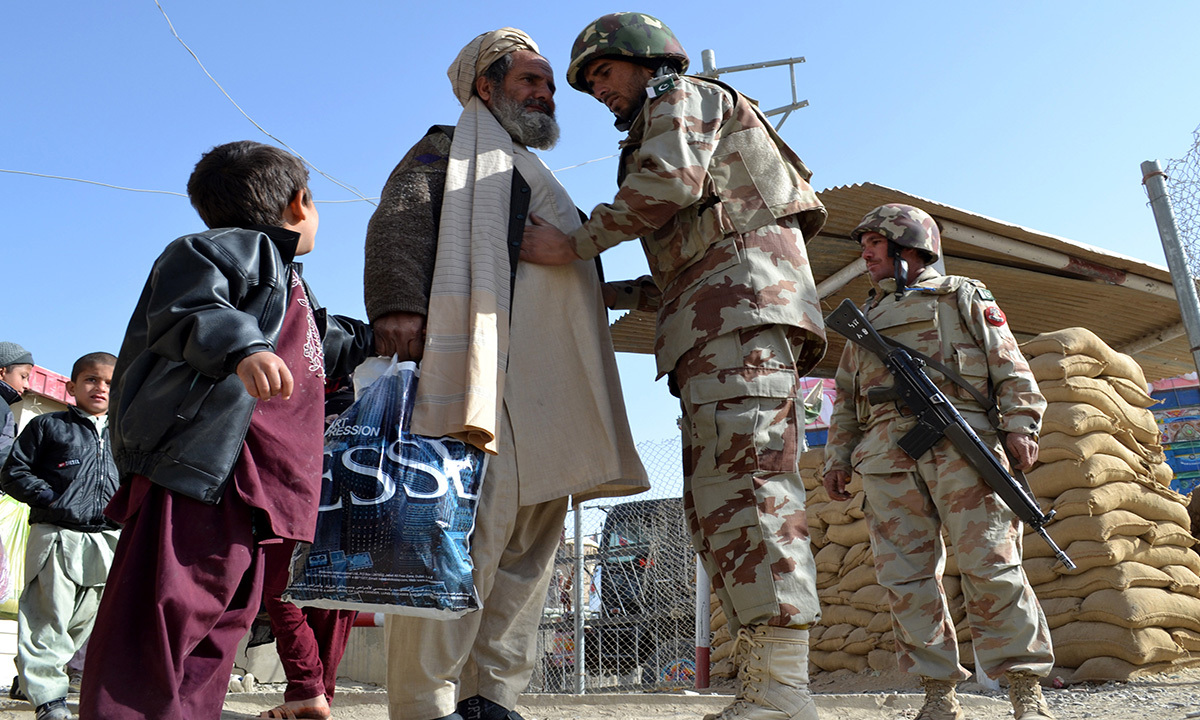 An elderly man coming from Afghanistan goes through routine border security check by an officer.