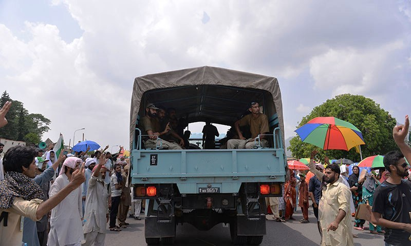 """Supporters of Pakistan Awami Tehreek chief Dr Tahirul Qadri gather as security personnel arrive in front of the Parliament during the """"Revolution March"""" protest in Islamabad on August 20, 2014. — Photo by AFP"""