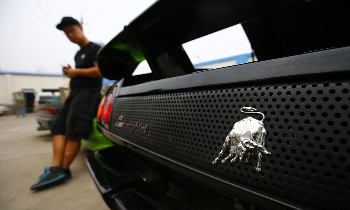 Wang Yu Stands Next To A Handmade Replica Of Lamborghini Diablo Outside A  Garage On The