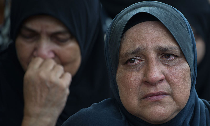 Noriah Daud (R) the mother of late co-pilot Ahmad Hakimi Hanapi, who perished aboard flight MH17 downed in eastern Ukraine, attends a burial ceremony in Putrajaya, outside Kuala Lumpur on August 22, 2014. — Photo by AFP