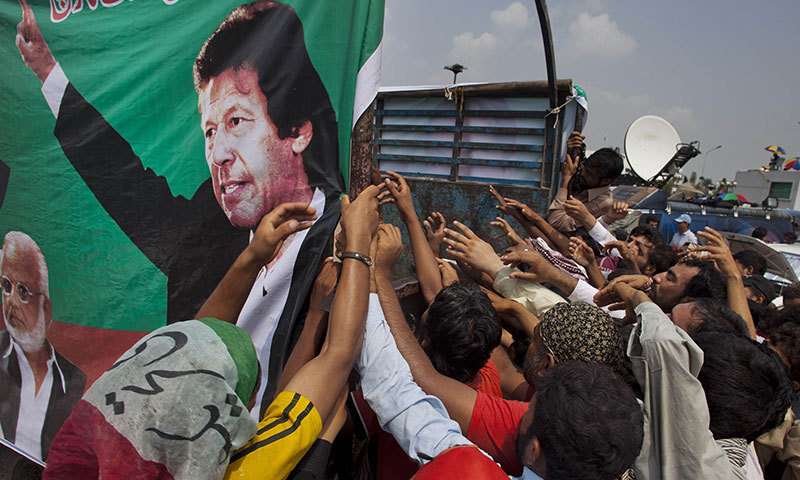Supporters of Imran Khan, shown in the banner, jostle to get food while in a rally in Islamabad, Aug 22, 2014. — AP