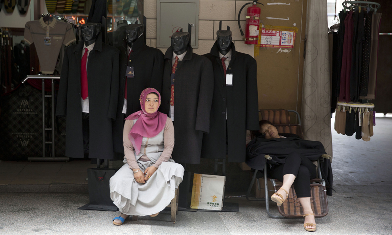 A Uighur woman waits for customers near a Han Chinese woman at a market in the city of Aksu in western China