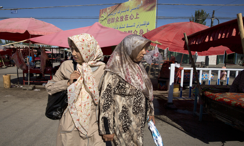 Uighur women in loose, full-length garments and headscarves associated with conservative Islam visit a market in Alaqagha in western China