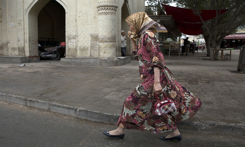 A Uighur woman walks past a mosque in the city of Kuqa in western China