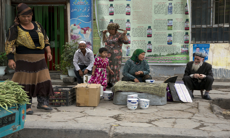 Uighur residents gather at a road side stall in the city of Aksu in western China