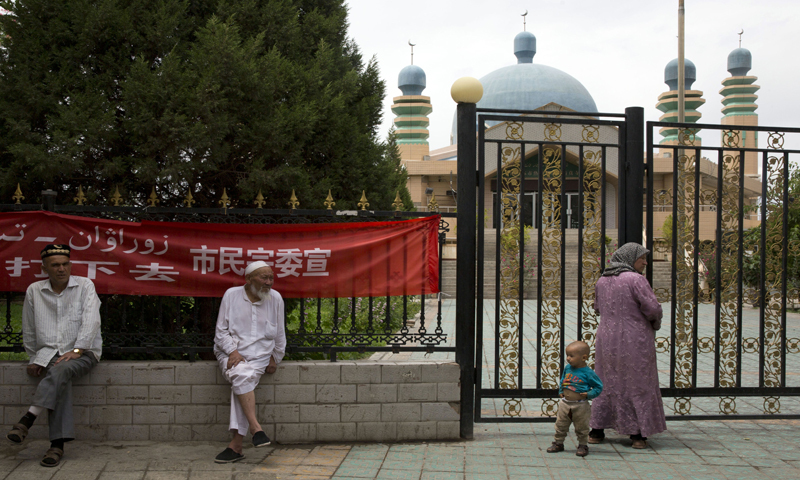 Uighur residents gather outside a mosque in the city of Aksu in western China