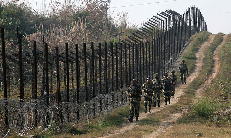 Photo from Dec 6, 2013 shows Indian Border Security Force (BSF) soldiers patrolling the fenced border with Pakistan at Babiya village in Hira Nagar sector.—Reuters photo