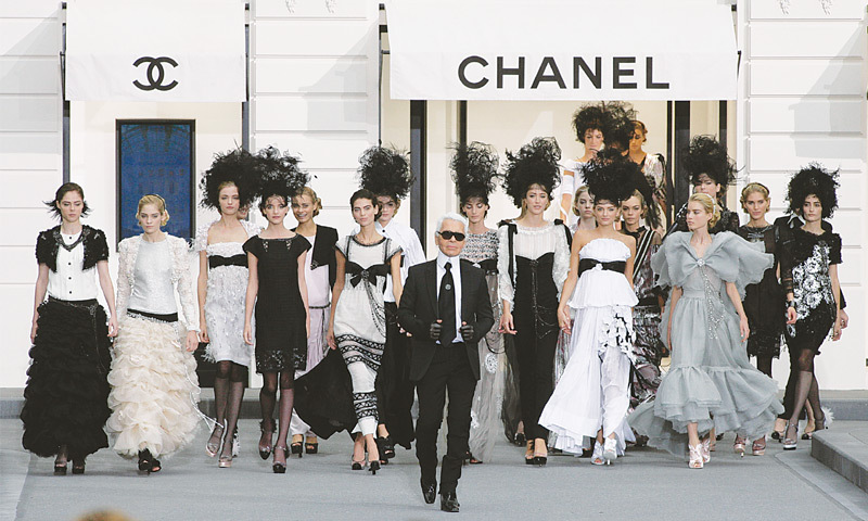 The creative director of the house of Chanel Karl Lagerfeld with models showcasing his collection.