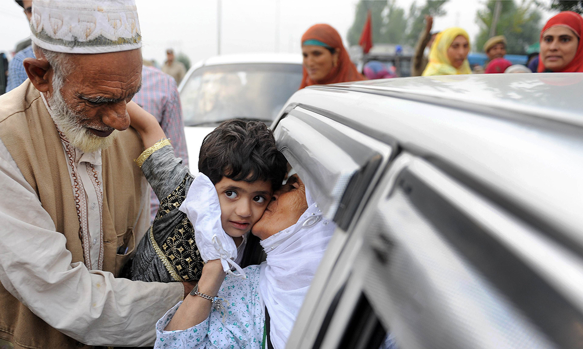 A Kashmiri pilgrim kisses a boy relative on her departure to Makkah for the annual Haj pilgrimage, in Srinagar. — Photo by AFP