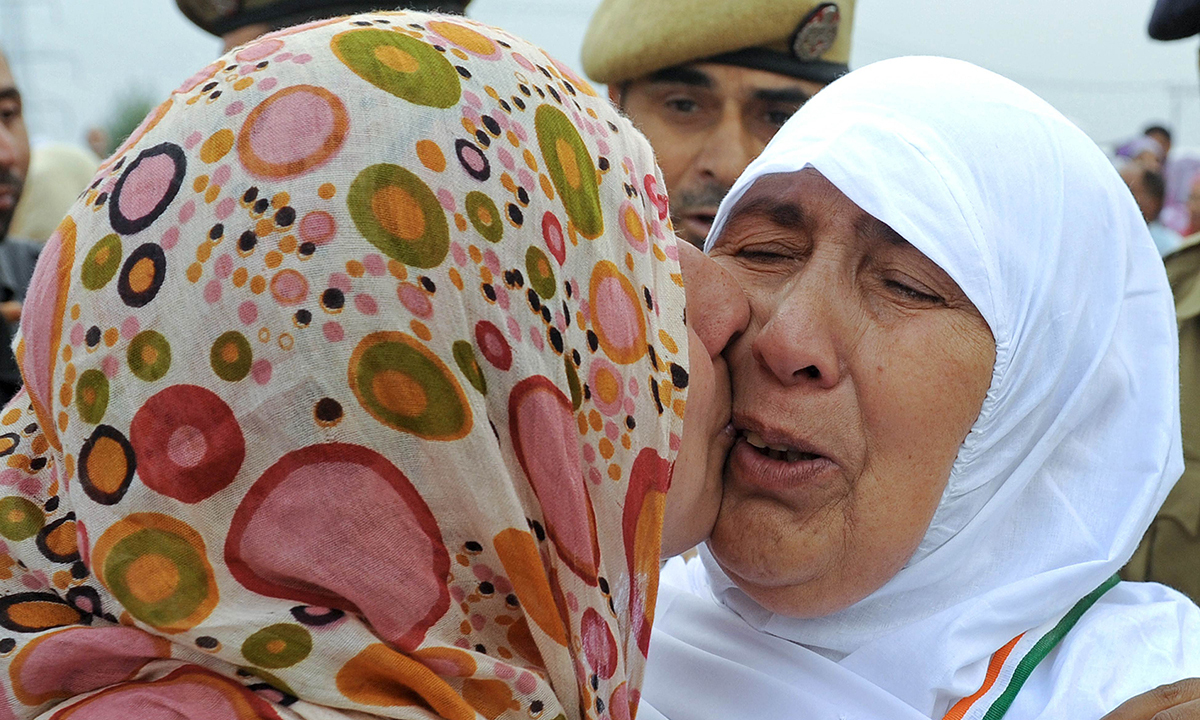 A Kashmiri pilgrim receives a kiss from a relative before she departs for Makkah for the annual Haj pilgrimage, in Srinagar. — Photo by AFP