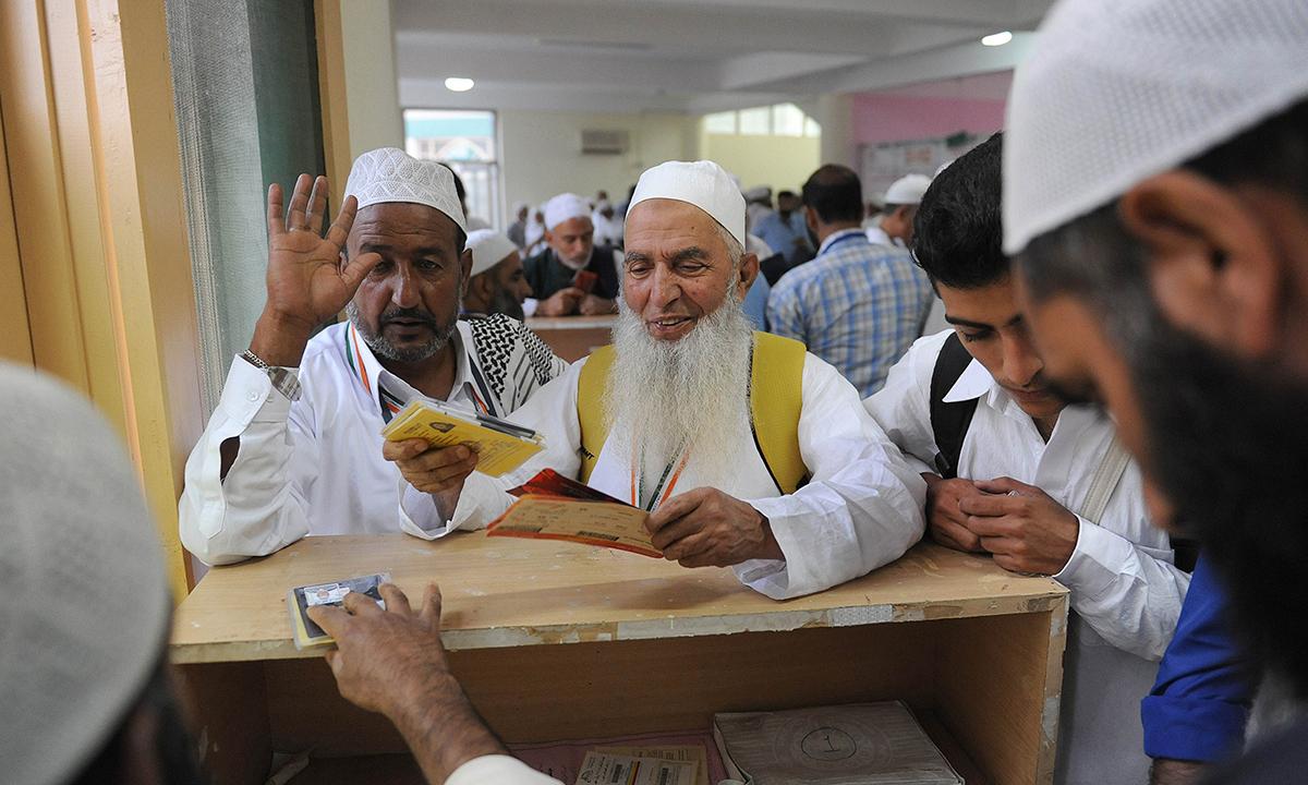 Kashmiri pilgrims receive their documentation prior to their departure to Makkah for the annual Haj pilgrimage, in Srinagar. — Photo by AFP