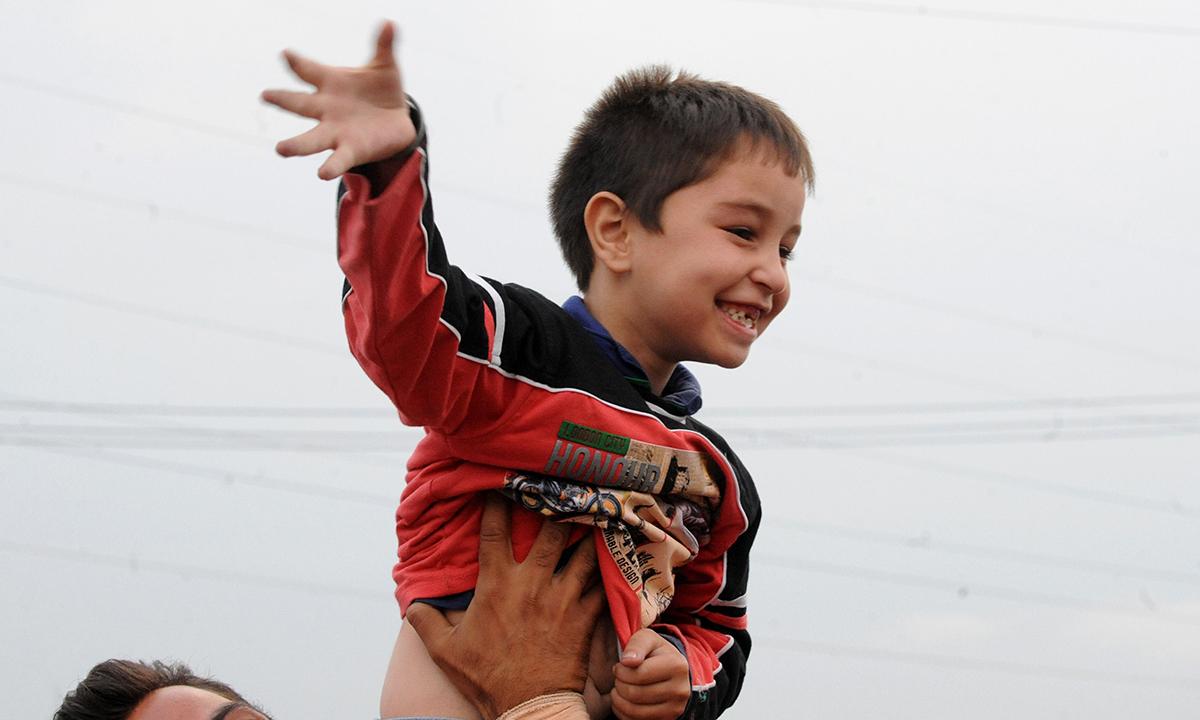 A child waves as Kashmiri pilgrims depart for Makkah for the annual Haj pilgrimage, in Srinagar. — Photo by AFP