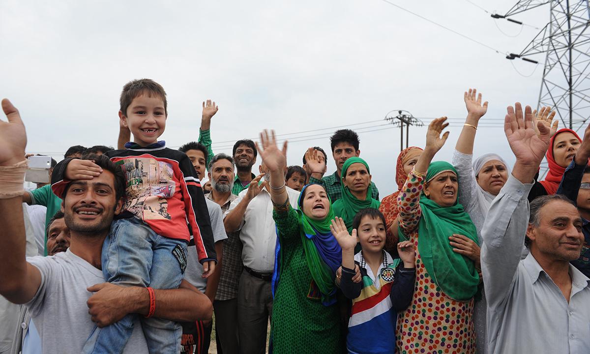 Kashmiri muslims wave as pilgrims depart for Makkah for the annual Haj pilgrimage, in Srinagar. — Photo by AFP