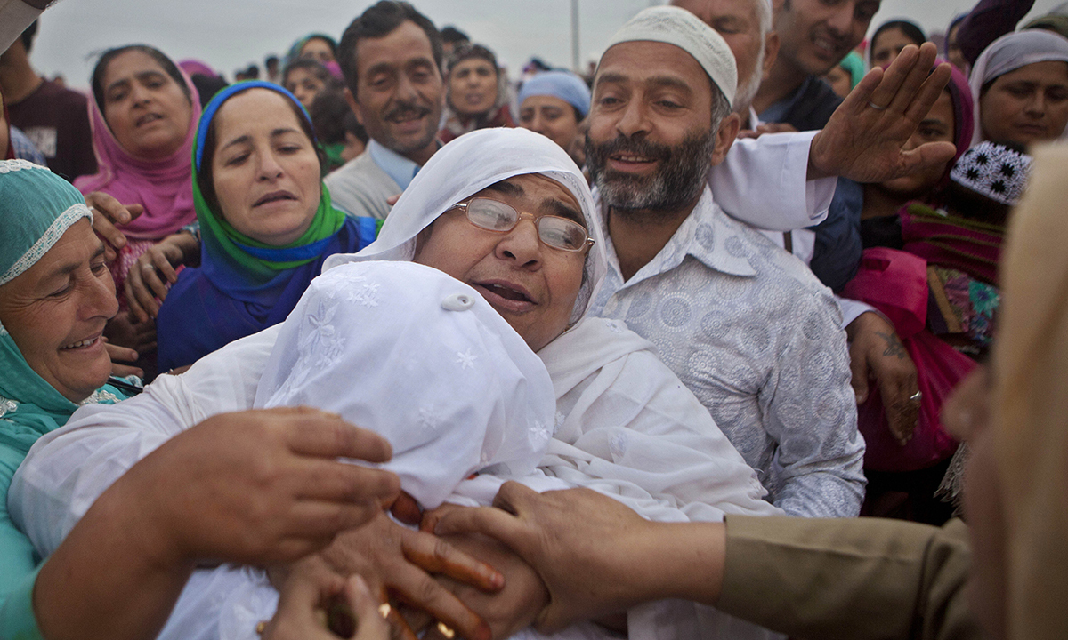 A Kashmiri Muslim pilgrim, back to camera, is hugged by her relative as she leaves for the annual haj pilgrimage to the holy city of Makkah, in Srinagar. — Photo by AP