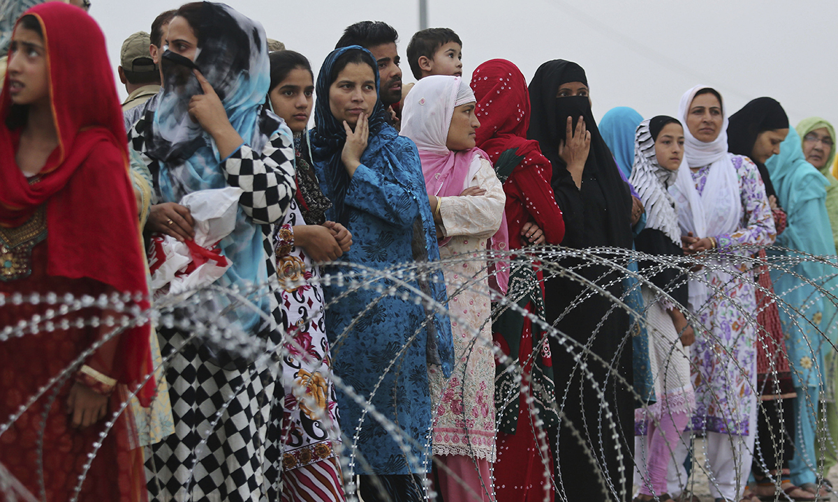 Kashmiri Muslims, standing behind a barbed wire, watch their relatives leave for the annual haj pilgrimage to the holy city of Makkah, in Srinagar. — Photo by AP