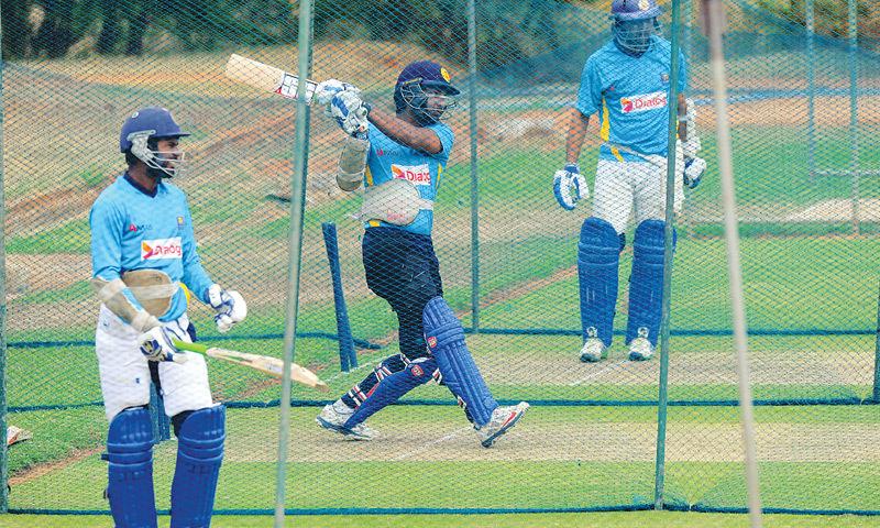 Sri Lanka's veteran batsman Kumar Sangakkara (R) bats in the nets as his team-mate looks on.—AFP