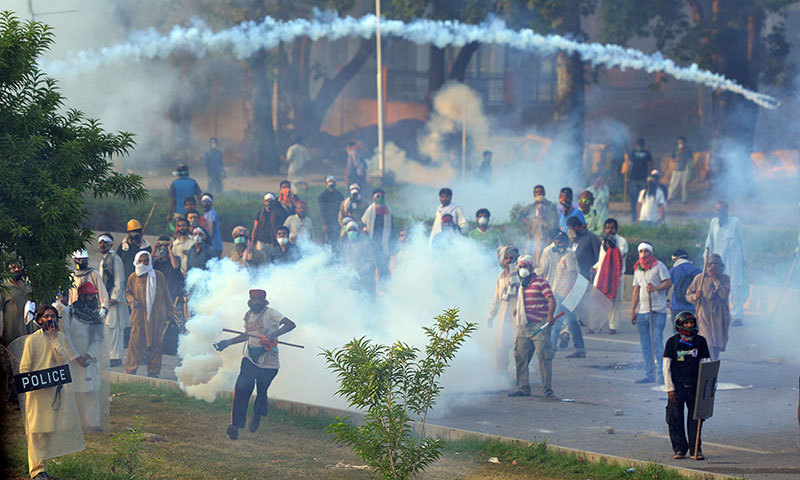 Supporters of Qadri return a tear gas shell towards police during clashes with security forces in Islamabad. — Photo by AFP