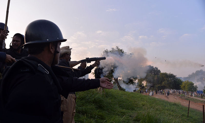 Riot police protect themselves from tear gas during clashes with the supporters of cricketer-turned-politician Imran Khan and Canadian cleric Tahir ul Qadri near the prime minister
