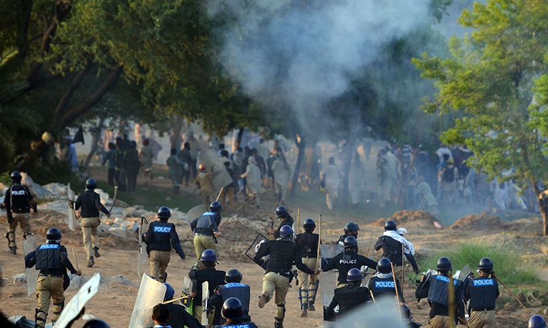 Riot police run towards supporters of Imran Khan and Canadian cleric Tahirul Qadri during clashes near the prime minister's residence in Islamabad on August 31, 2014. — AFP