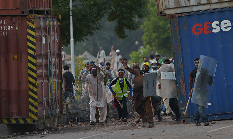Supporters of Imran Khan and Canada-based Pakistani cleric Tahirul Qadri throw stones towards riot police during clashes near the prime minister