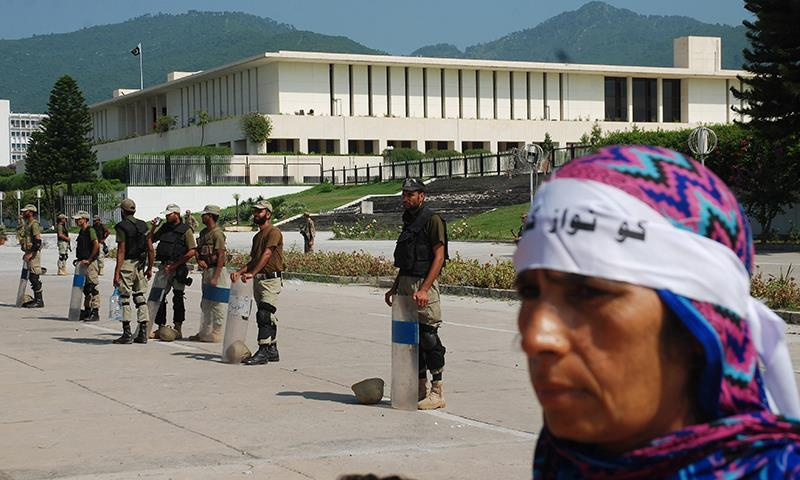 """Troops of Pakistan's paramilitary force stand guard outside the Parliament building as a protester walks past them with a headband that reads, """"go Nawaz go,"""" in Islamabad, Aug 31, 2014. — Photo by AP"""