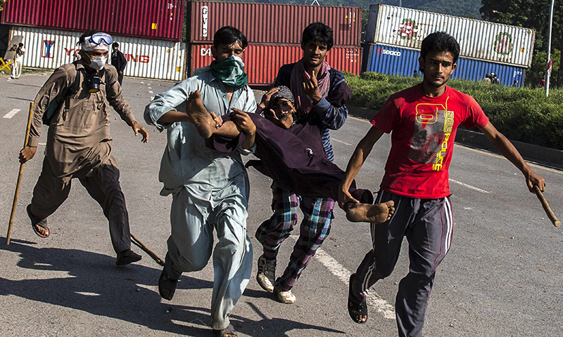 Supporters of Tahirul Qadri carrying an injured fellow protester. — Reuters